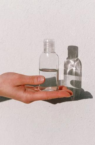 Hand holding clear bottle of disinfectant