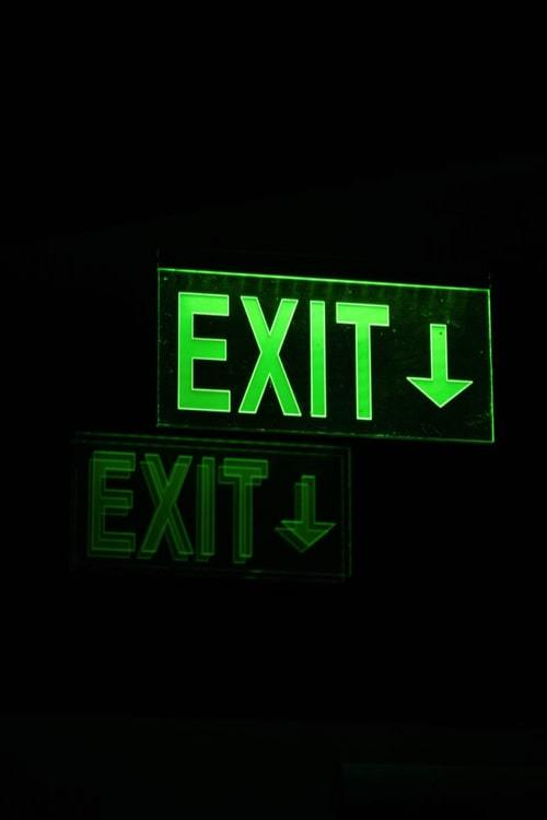 Emergency exit light signal in green on black background